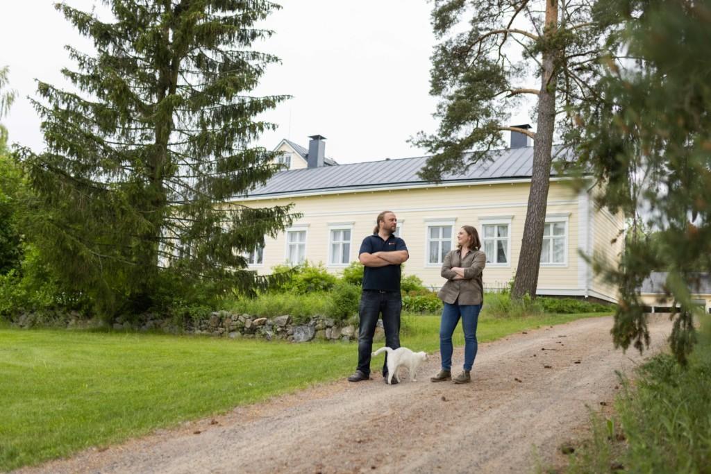 Mies ja nainen seisovat vanhan pohjalaistalon edustalla ja katsovat toisiaan. Heidän jaloissaa on kissa.